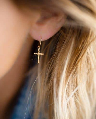 Femme portant des boucles oreilles créoles en forme de croix fine en or de la marque Luj Paris Made in France