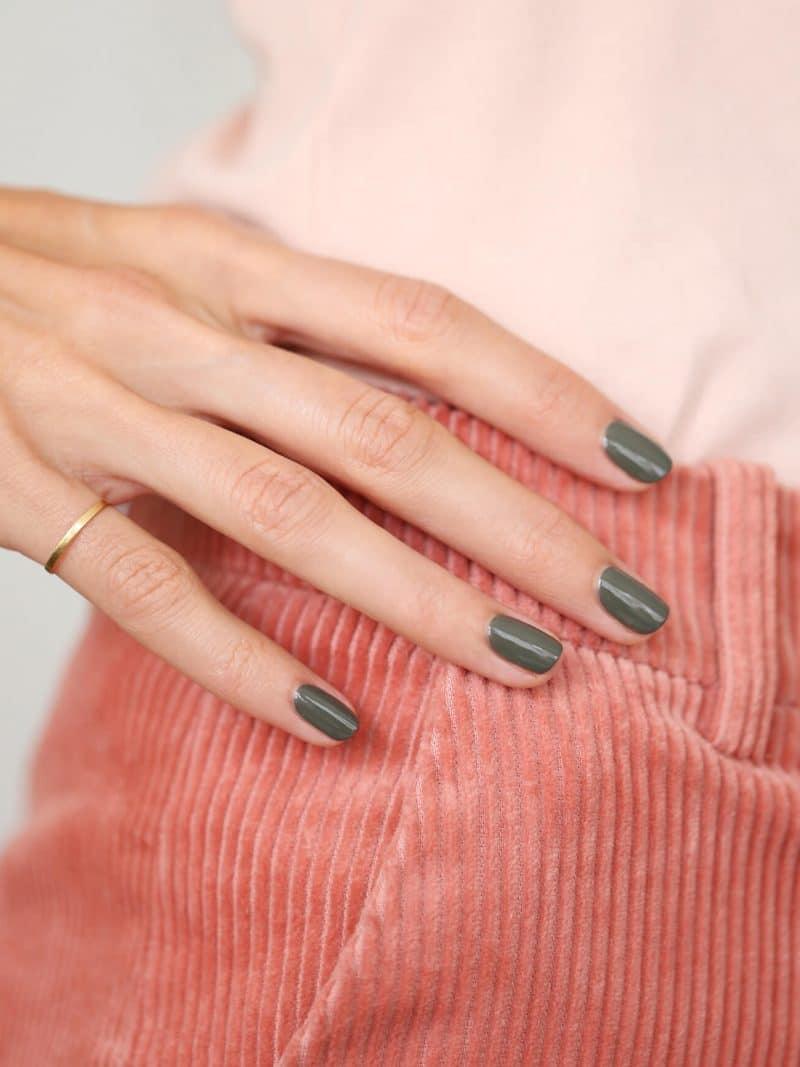 Femme portant un vernis à ongles bio green de la marque Manucurist de couleur vert khaki
